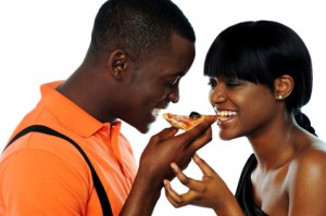 Young couple sharing a slice of pizza