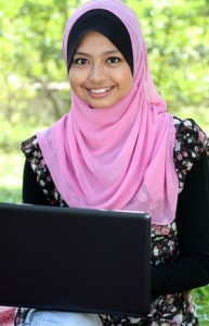 Beautiful muslim woman using laptop while sitting relaxed